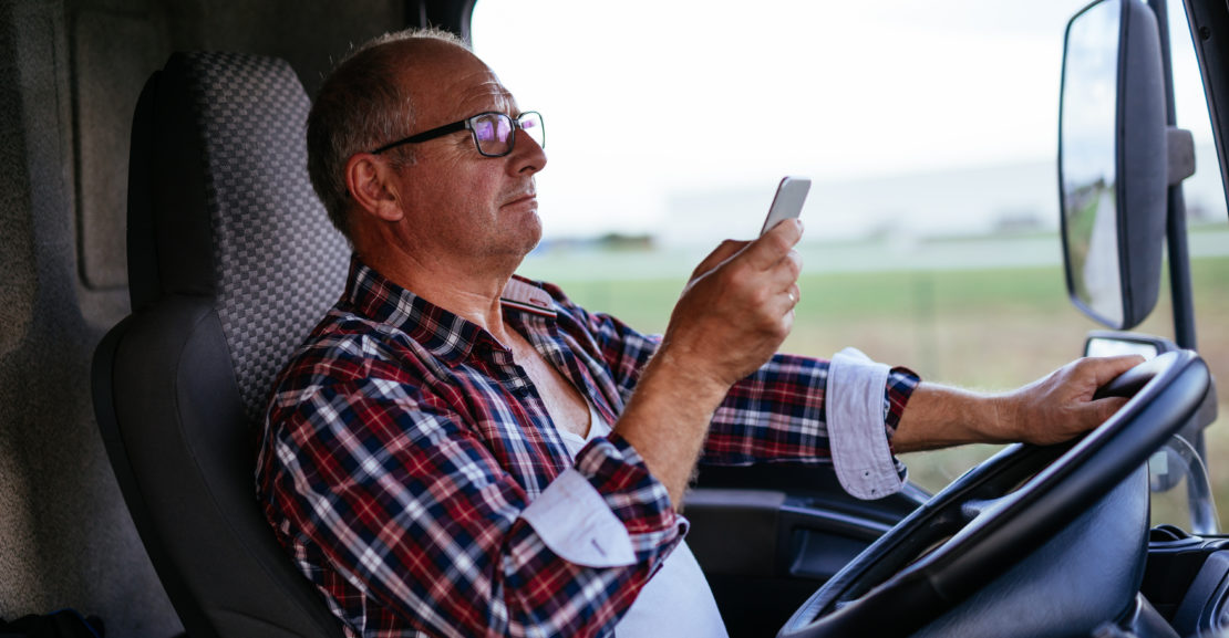 Senior man driving a truck and texting on a mobile phone.