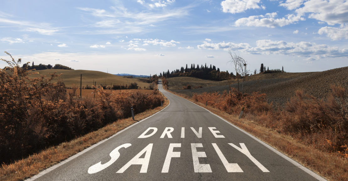Concept drive safely message on the sunny summer asphalt country road. Conceptual safe driving alert background.